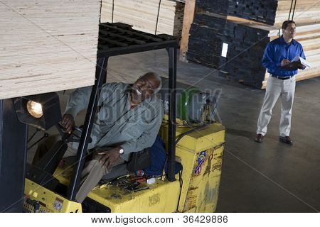 Happy senior man driving forklift