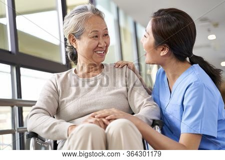 Friendly Caregiver Of Nursing Home Talking To Asian Senior Woman In Hallway