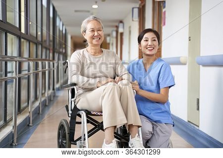 Asian Senior Woman And Her Caregiver Looking At Camera Smiling