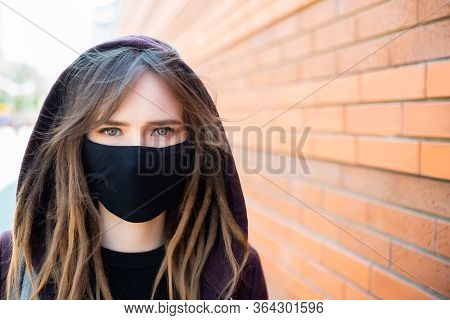 Close-up Portrait Of Girl With Dreadlocks And Green-blue Eyes, Wearing Medical Flu Mask And Hooded S