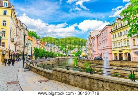 Karlovy Vary, Czech Republic, May 10, 2019: People Are Walking Down Street And Tepla River Embankmen