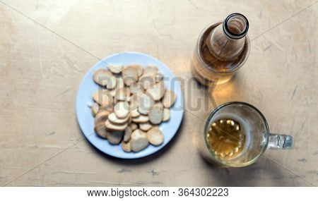 Rusks In A Plate, A Beer Mug, And A Bottle With Cider On The Table Top View. Soft Focus Concept.