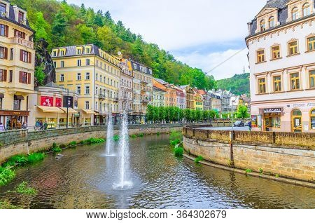 Karlovy Vary, Czech Republic, May 11, 2019: People Are Walking Down Street And Tepla River Embankmen
