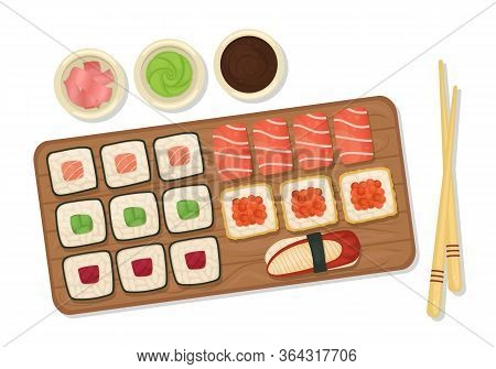 Set Of Sushi And Rolls On A Wooden Board With Soy Sauce, Wasabi And Ginger. Japanese Food. Flat Lay