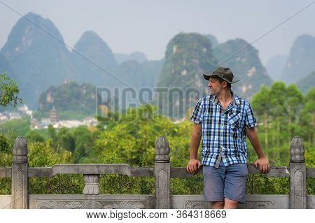 A View Of A Male Laying On The Fence And Enjoying The Beautiful View Of The Karst Mountains In Yangs