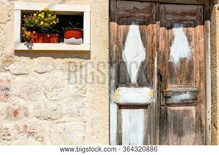Authentic House With A Stone Wall And A Beautiful Door And Flowerpots With Flowers At The Entrance,