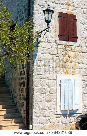 An Authentic House With A Stone Wall, With Beautiful Old Windows And With White And Brown Shutters,