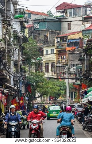Hanoi, Vietnam, December 30, 2019, Tourists and bikers on a street of the old quarter