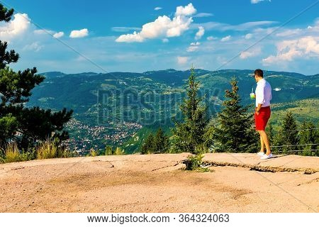 A Young Guy Looks Down At The Valley And The Mountains Standing On A High Point