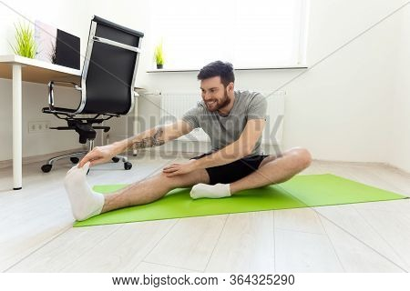 Man Stretching At Home. Man Doing Exercises At Home. Home Workout. Man Doing Sports At Home. Home Sp