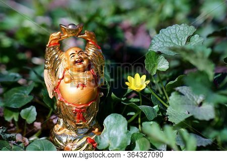 Buddha Statue In Wild Flowers. The Symbol Of Feng Shui.