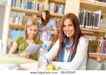 Young female students at library study room high school