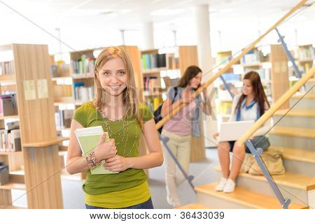 Female teenager student in green top standing at high-school library