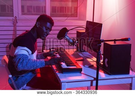 Music Production Concept - Male Sound Producer Working In Home Recording Studio.