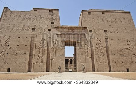 Hieroglypic Carvings On Wall At The Entrance Pylon Gate To Ancient Egyptian Temple Of Horus In Edfu