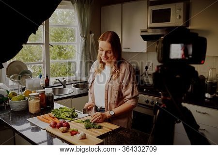 Woman In Modern Kitchen Chopping Fresh Green Vegetables To Record Food Recipe On Vlog - Young Woman
