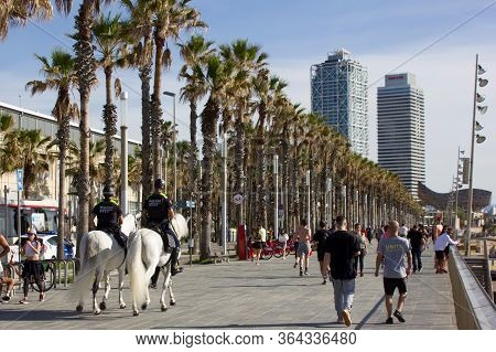 Barcelona, Spain, 03 May 2020: Two Police Officers On Horses On The Barcelona Beach Promenade Watchi