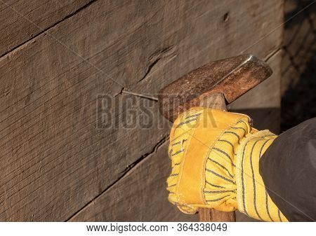 Yellow Glove With A Hammer Knocks The Nail Into The Plank