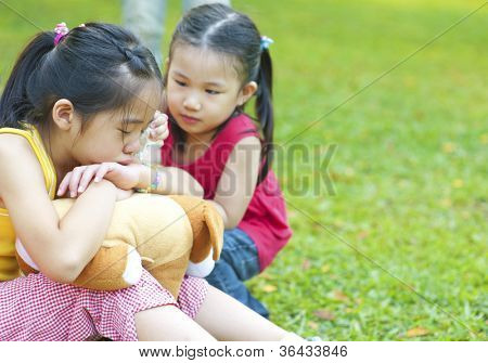Little girl is comforting her crying sister