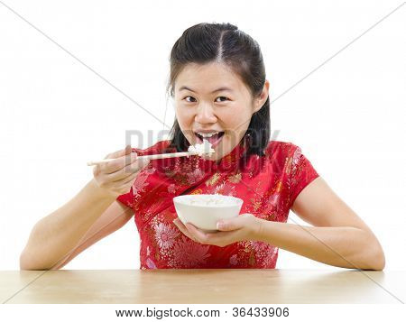 Asian woman eating rice with chopsticks over white background poster