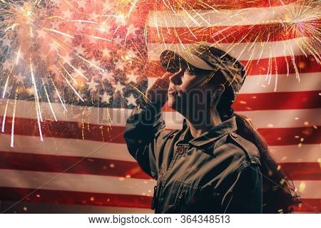Memorial Day. A Female Soldier In Uniform Salutes Against The Background Of The American Flag With F