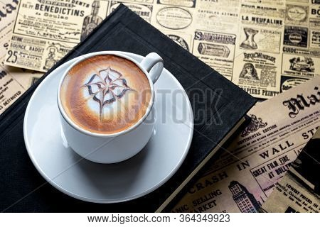 A Small Cup Of Cappuccino On A Saucer Is Set On A Book On A Table With Old Newspapers Spread Out. Dr