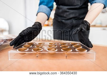 Chef Or Chocolatier Shakes Chocolate Molds For Sweets