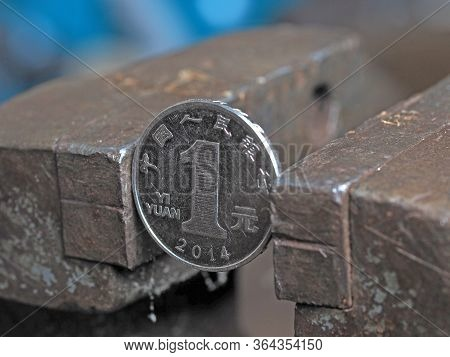 Yuan Coin Clamped In A Metal Vise. Currency Under The Onslaught, The Concept Of Financial Problems A