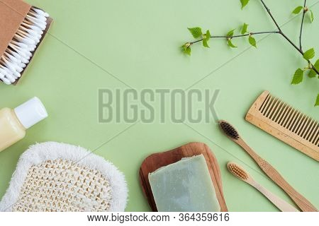 Plastic Free Bathroom Accessories On Green Background. Bamboo Toothbrushes, Shampoo Bottle, Cotton B