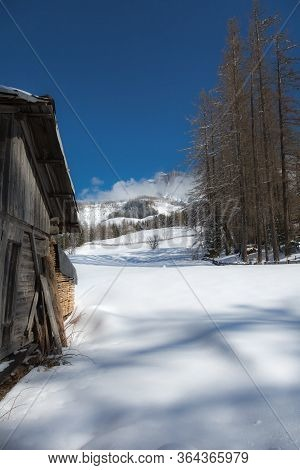 Wooden Shack In Winter Day With Fresh Snow In The Mountains.