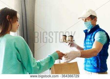 Woman Receiving Packages From Delivery Man. Courier In Uniform Face Mask Gloves Holding Paper Boxes