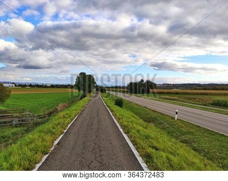 Country Road Through Rural Landscape With Blue Sky And Clouds