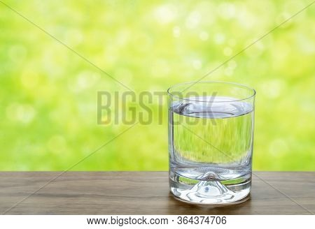 Purified Fresh Drink Water In Clear Glass Next Window With Blurred Raindrop And Bokeh Background.gla