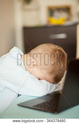 Boy Kid Sitting On The Desk With A Digital Tablet Laptop Notebook. He Very Tired And Fell Asleep. Ki
