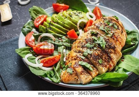 Grilled Chicken Breast And Avocado Salad With Spinach And Cherry Tomatoes On Black Stone Background.