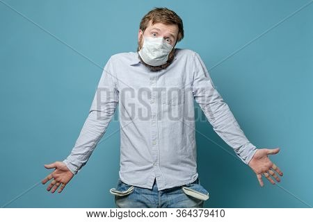 No Money. Perplexity Man In A Medical Mask With Empty Pockets And A Questioning Look. Concept Of Eco
