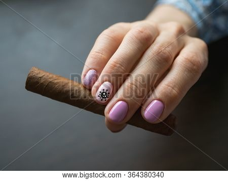 Cigar In Woman Hand, Photo On Gray Background. Creative Manicure With Painted Virus On The Nails, So