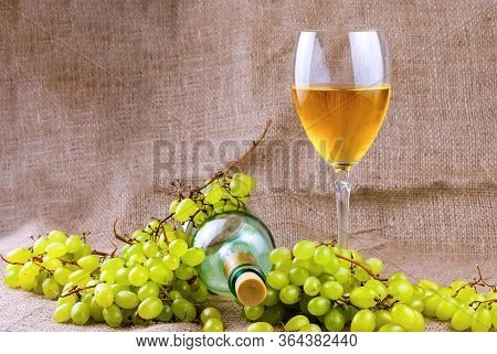 Bunch Of Grapes, Glass Bottle And Glass Of White Wine On Burlap Fabric Background