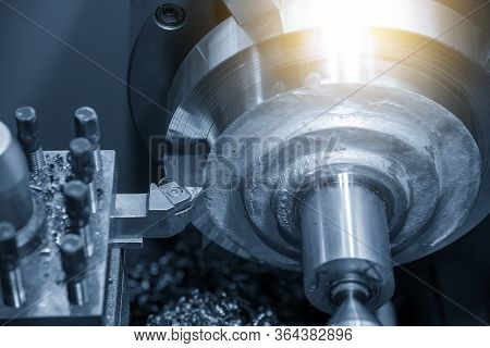 The Operation Of Lathe Machine Rough Cutting The Metal  Parts With Lighting Effect In The Light Blue