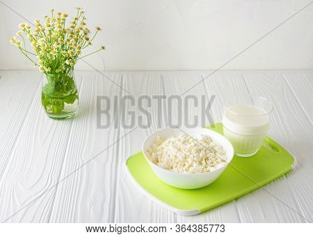 Homemade Kefir And Fermented Dairy Product Curd On A White Wooden Background With Flowers . Horizont