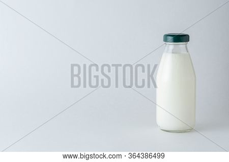 One Glass Bottle Of Homemade Kefir On A White Background With Copy Space. Organic Probiotic Cold Fer