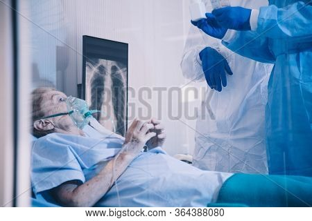 Infected Patient On Takecare Of Doctor And Nurse With X-ray Lung In Quarantine Lying On Bed In Hospi