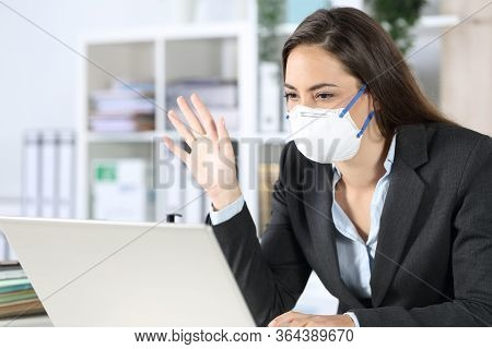 Happy Executive Woman Looking At Laptop Webcam On Videocall Greeting Avoiding Covid-19 With Mask Sit