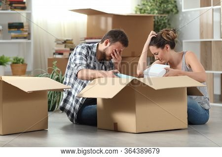 Two Sad Evicted Tenants Moving Home Boxing Belongings Sitting On The Floor