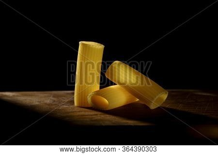 Rigatoni, Typical Italian Pasta Arranged On A Wooden Table Crossed By A Beam Of Light On A Dark Back