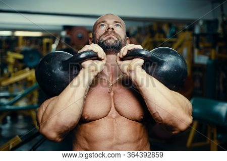 Bodybuilder Pumping Up Chest Muscles With Kettlebell