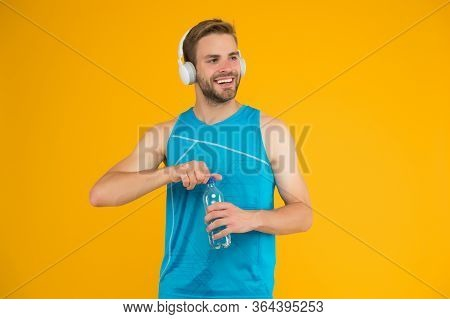 Celebrating Health. Healthy Man Open Water Bottle. Fitness Coach Wear Headphones. Water And Hydratio