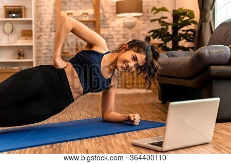 20s Young Asian Woman In Sportswear Doing Stretching Exercises While Watching Fitness Training Class