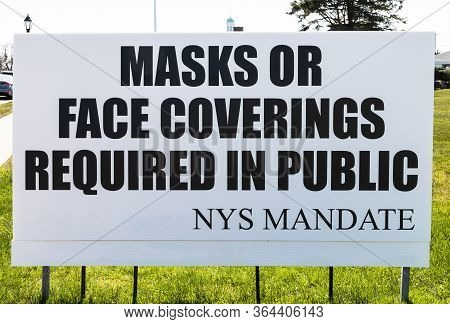 A Sign On The Side Of The Road Reads Mask Or Face Covering Required In Public As You Enter A Village