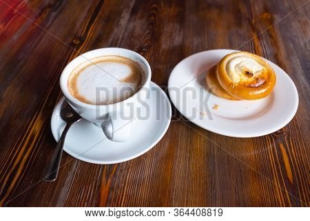 Cup With Cappuccino And Saucer With A Bun View From A High Point. Bun With Cottage Cheese And Cappuc
